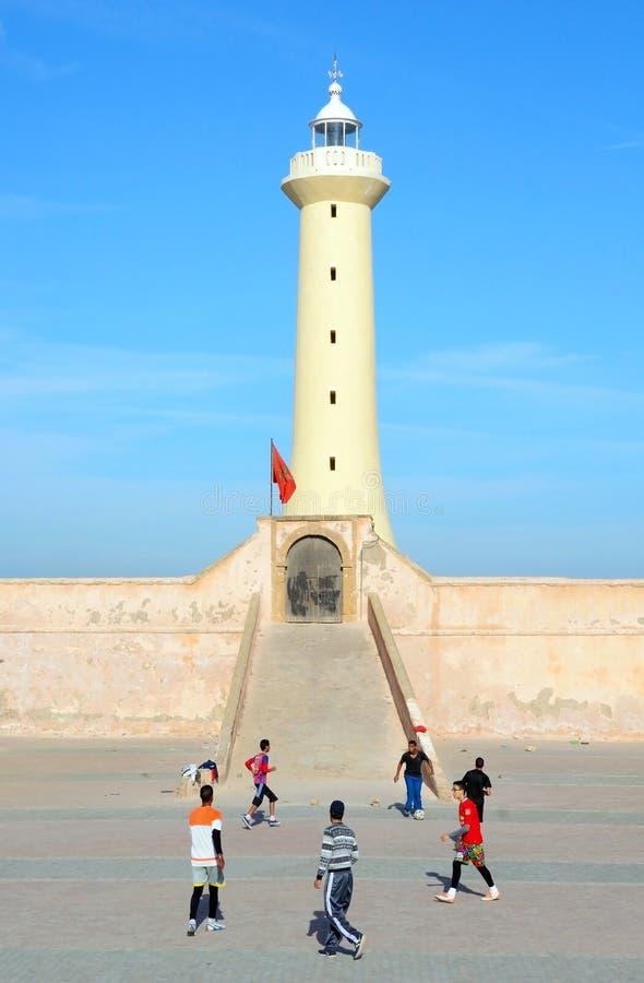 As juventudes marroquinas que jogam o futebol do futebol fronteiam o farol na costa atlântica de Rabat, Mo imagens de stock royalty free