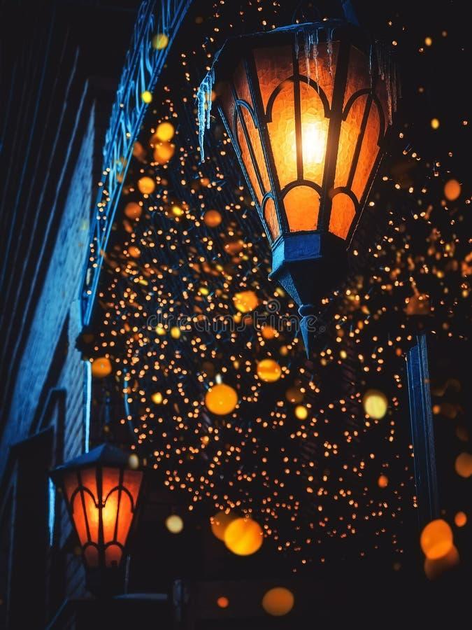 As lanternas velhas mágicas de uma rua brilham na rua na noite Muitas luzes brilhantes ao redor Lanternas clássicas O do ferro da fotografia de stock royalty free
