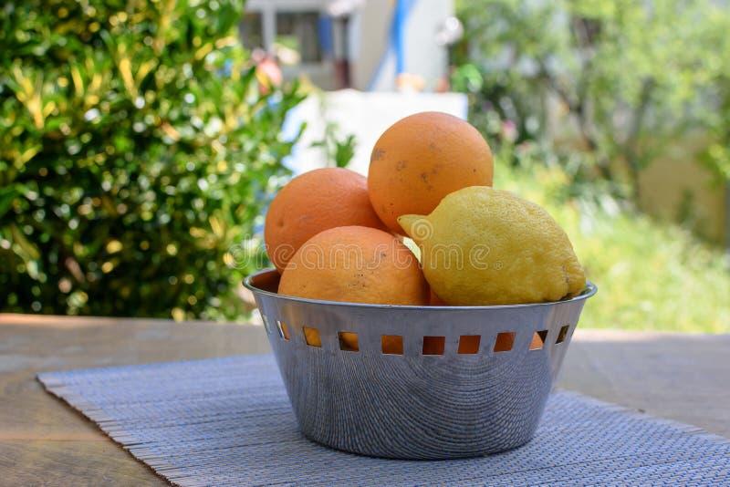 As laranjas e os limões encontram-se em um copo na tabela fotos de stock royalty free