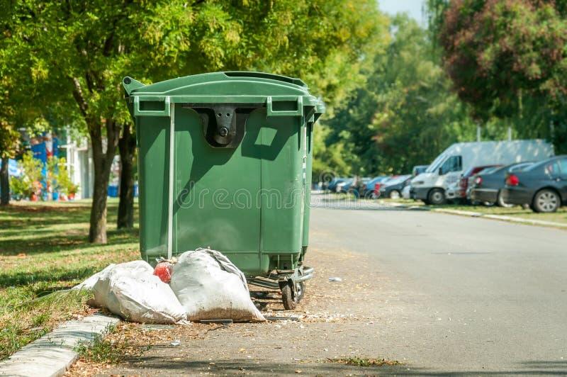 As latas de lixo verdes plásticas na rua na cidade com sucata ensacam completamente da maca na estrada asfaltada imagem de stock