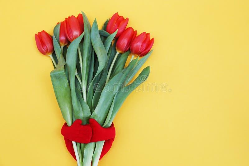 As legen Anordnung für die roten Tulpen, die in Form durch ein Spielzeug des Herzens auf ein gelbes backgound umarmt werden lizenzfreie stockbilder