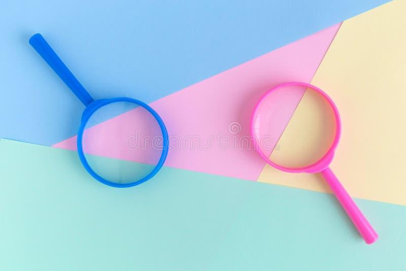 As lentes de aumento no fundo pastel procuram o conceito minimalistic fotos de stock