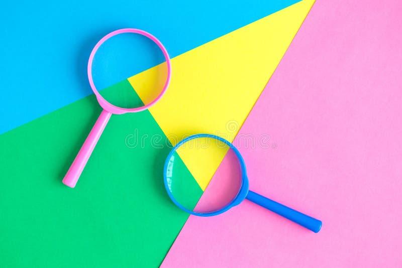 As lentes de aumento no fundo pastel procuram o conceito minimalistic fotografia de stock