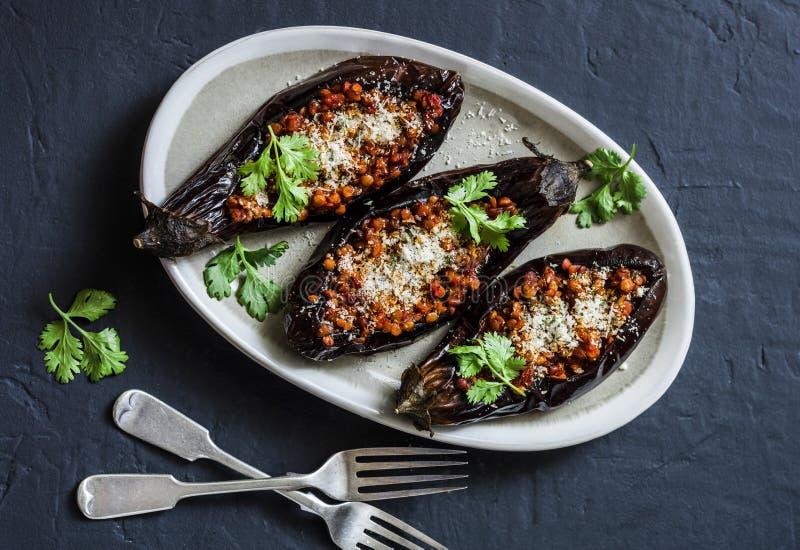 As lentilhas enchidas roasted a beringela - almoço saudável delicioso do vegetariano, petisco, aperitivo em um fundo escuro imagens de stock