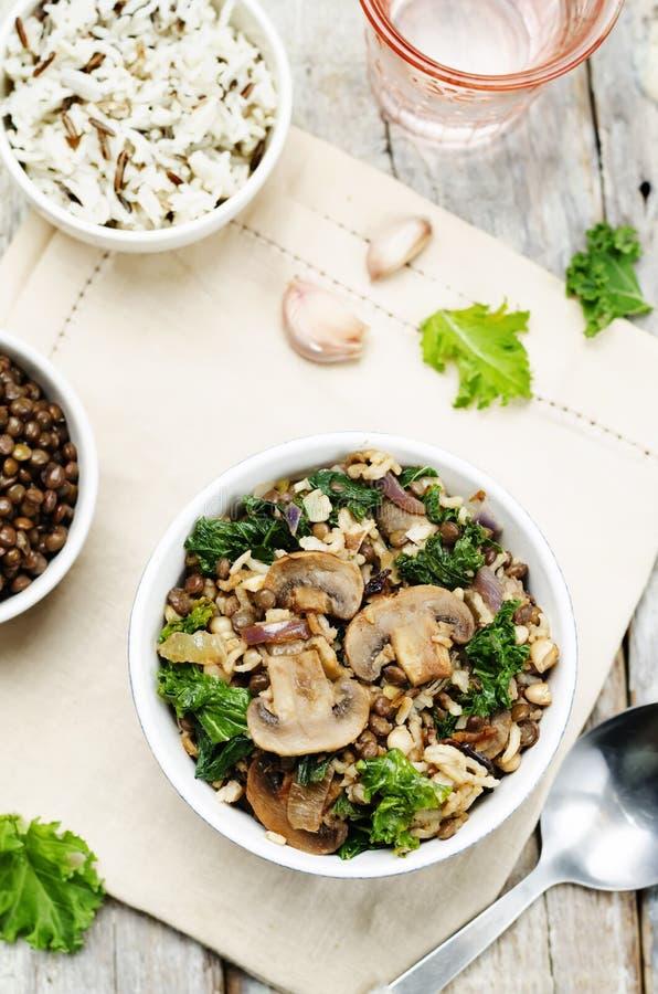 As lentilhas verdes da couve crescem rapidamente arroz branco e selvagem fritado foto de stock