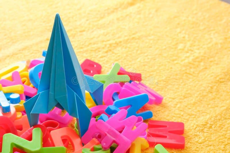 As letras coloridas do alfabeto com o origâmi azul do brinquedo sobem rapidamente Conceito da instrução foto de stock royalty free