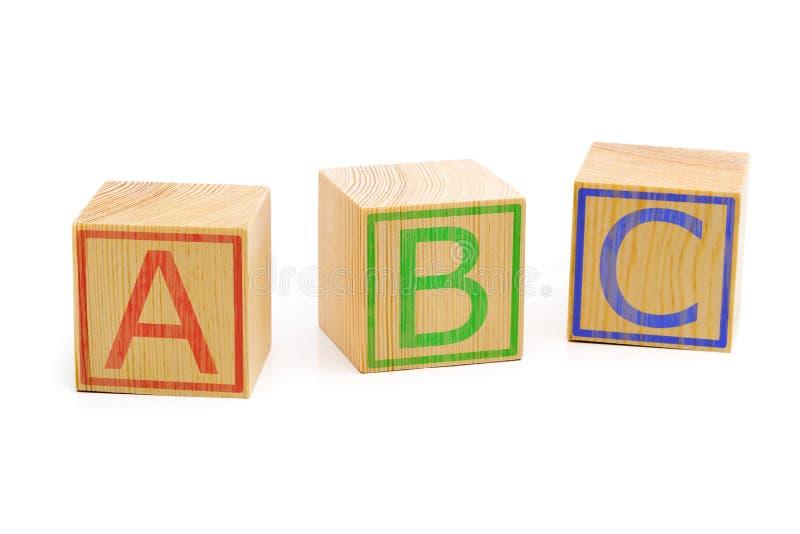 As letras de ABC em três cubos de madeira marrons alinharam imagens de stock royalty free