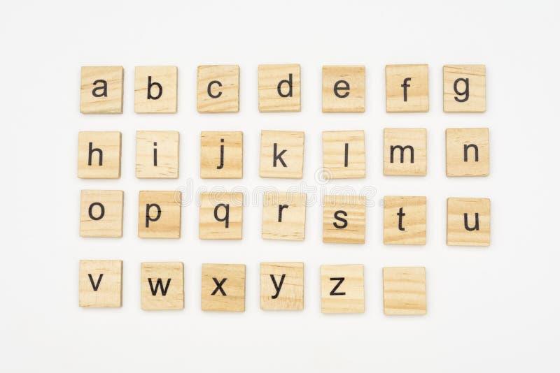 As letras Lowercase do alfabeto escarafuncham sobre blocos de madeira fotografia de stock royalty free