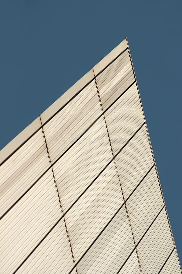 As linhas e a textura dos retângulos formaram na parede do metal branco da construção foto de stock