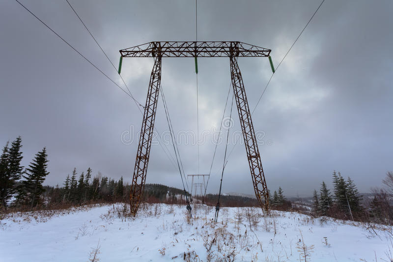 As linhas elétricas da transmissão da eletricidade na alta tensão do fundo do inverno elevam-se Pilão da transmissão da eletricid foto de stock