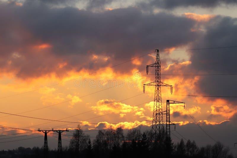 As linhas elétricas de alta tensão cruzam a estação elétrica do mestnost montanhoso no verão sob o céu aberto Indústria prendida  imagem de stock royalty free
