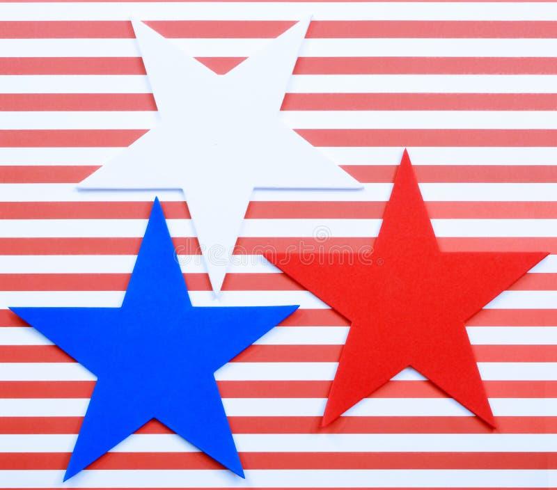 As listras horizontais vermelhas e brancas alegres formam o fundo atrás de 3 formas da estrela do entalhe da espuma imagens de stock royalty free