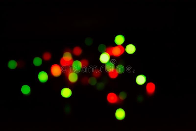 As luzes coloridos obscuras do fulgor da festão verde e vermelho na obscuridade fotos de stock