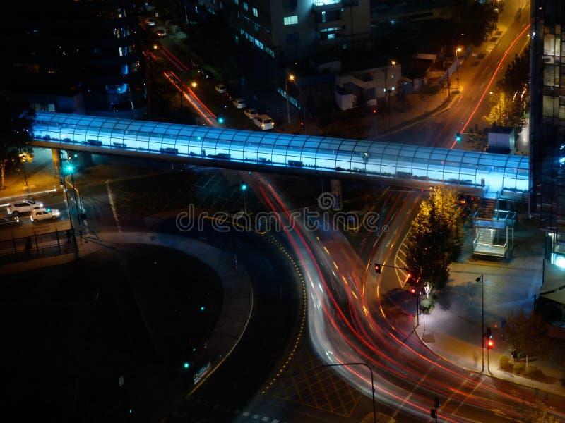 As luzes da noite de um brigde pedestre no citi de Santiago de Chile de cima com do traço de carro iluminam a exposição longa fotografia de stock