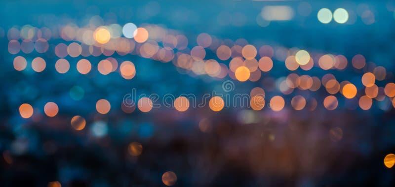 As luzes de borrão da cidade abstraem o bokeh circular no fundo azul imagem de stock
