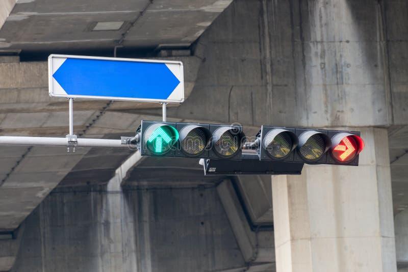 As luzes de sinal do tráfego são setas vermelhas para parar o carro e as setas verdes a ir com nomes da rua embarcam imagem de stock royalty free