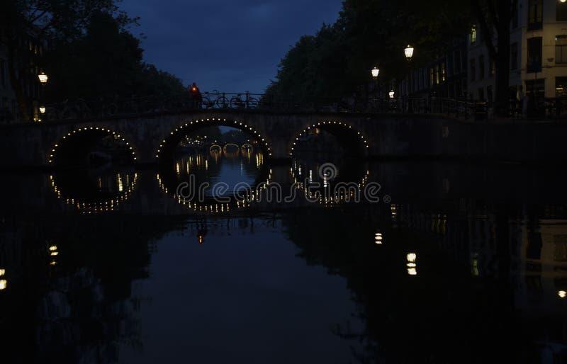 As luzes em pontes arqueadas são refletidas na água do canal de Amsterdão na noite imagem de stock royalty free