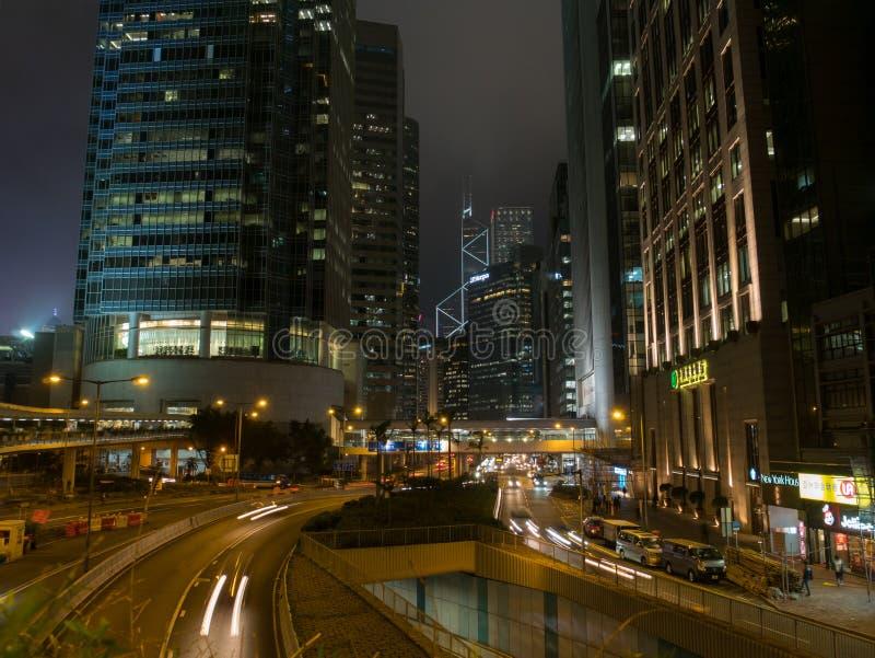 As luzes listam do tráfego com construções modernas do arranha-céus na cidade de Hong Kong na noite fotografia de stock royalty free