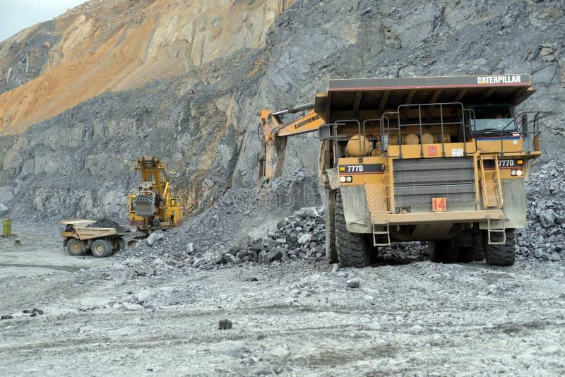 As máquinas escavadoras derramam o minério da nefeline em caminhões basculantes de Caterpillar em uma carreira imagens de stock royalty free