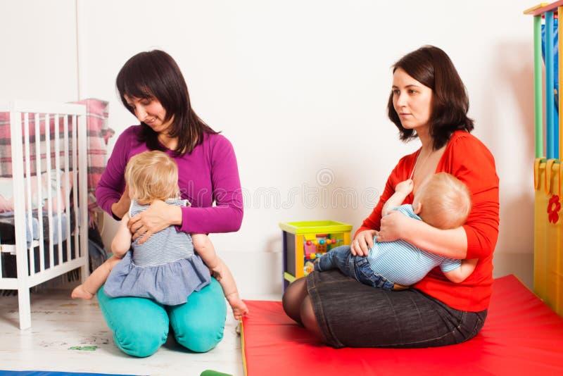 As mães estão amamentando as crianças foto de stock