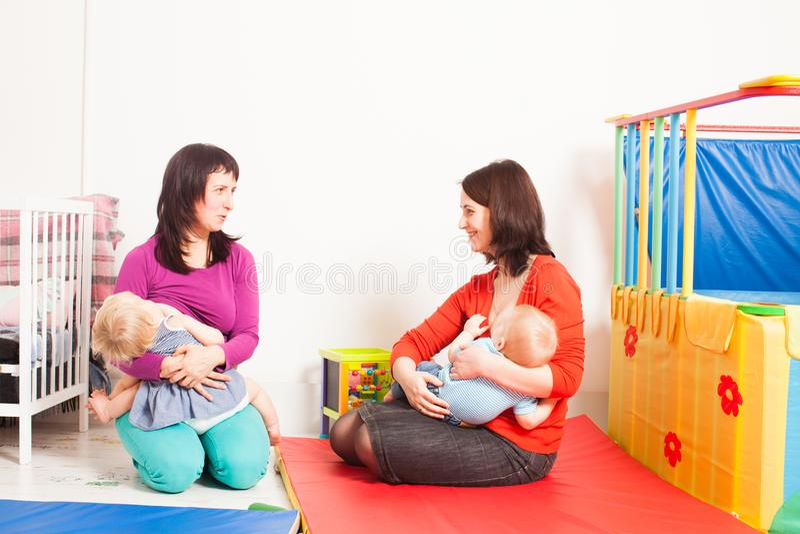 As mães estão amamentando as crianças fotografia de stock royalty free