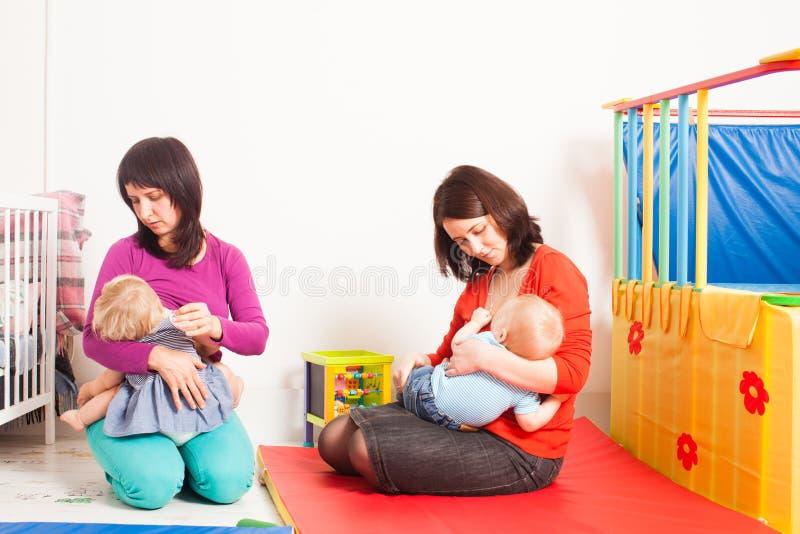 As mães estão amamentando as crianças imagens de stock royalty free