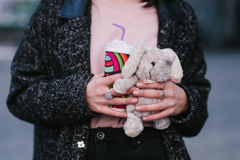 As mãos à moda novas da menina guardam o café e brinquedos quentes fotos de stock