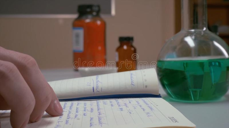 As mãos abrem e olhando algo em um diário, caderno mãos da escrita do cientista no caderno, mãos do ` s das mulheres, fazendo imagens de stock royalty free