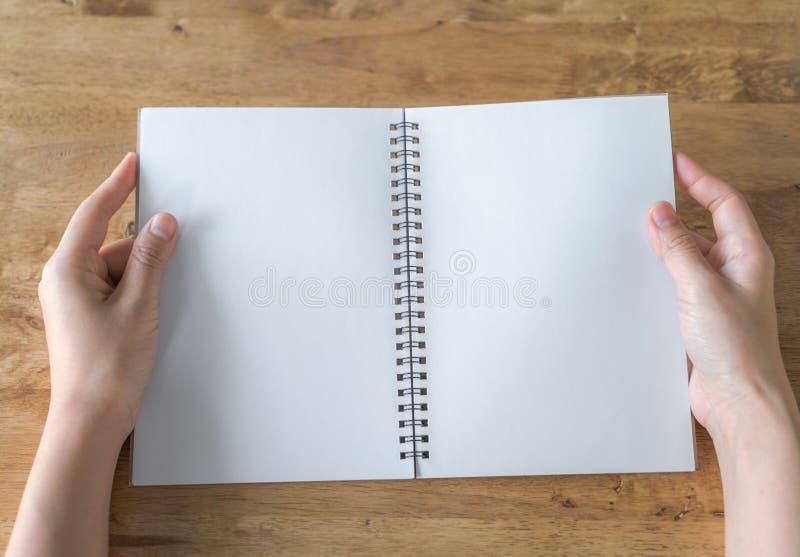 As mãos abrem o catálogo vazio, compartimentos, zombaria do livro acima na tabela de madeira foto de stock