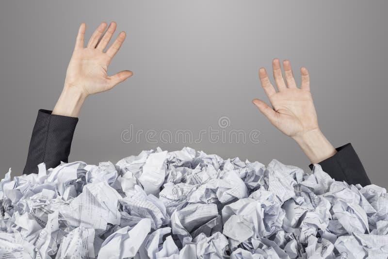 As mãos alcançam para fora do montão grande de papéis amarrotados imagens de stock