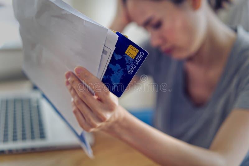 As mãos asiáticas da mulher que guardam o cartão de crédito e as contas preocupam-se sobre o dinheiro do achado para pagar o débi fotografia de stock