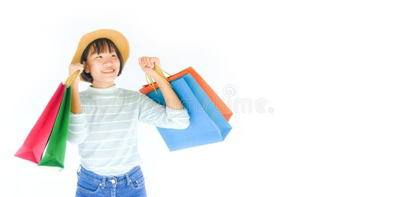 As mãos bonitas da menina da criança que guardam o saco de compras isolaram-se no fundo branco - verão feliz da jovem mulher asiá imagem de stock royalty free