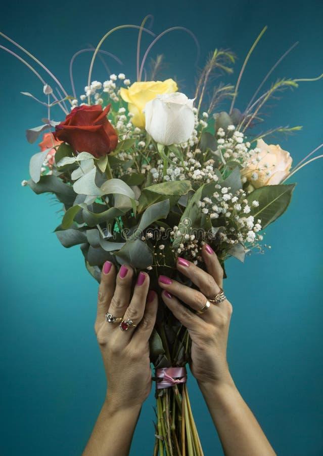 As mãos bonitas da mulher guardam um ramalhete grande das rosas fotos de stock royalty free