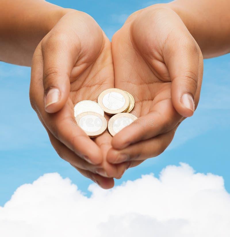 As mãos colocadas da mulher que mostram euro- moedas imagens de stock royalty free