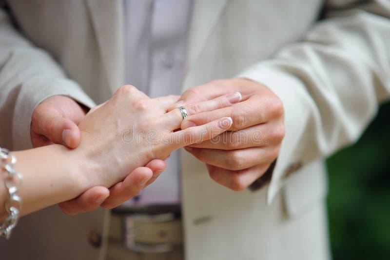 As mãos com anéis preparam a colocação do anel dourado sobre o dedo da noiva fotografia de stock royalty free