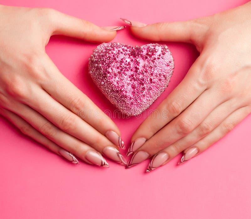 As mãos com manicure dobraram-se na forma do coração imagens de stock royalty free
