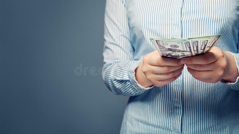 As mãos contam o dinheiro no fundo azul fotografia de stock