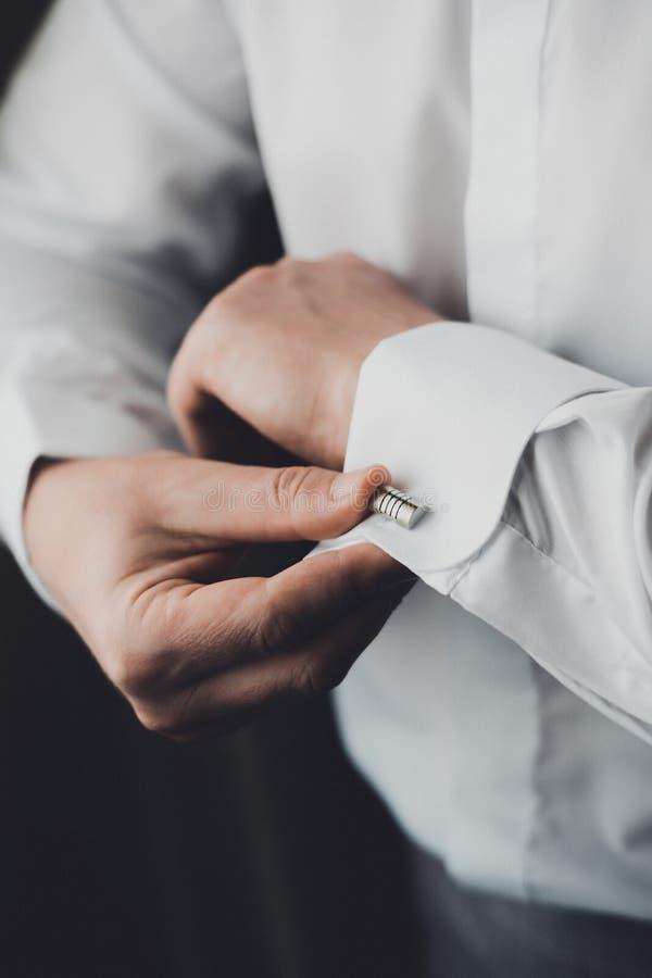 As mãos corrigem camisas de vestido brancas de fechamento dos punhos, noivo imagens de stock royalty free