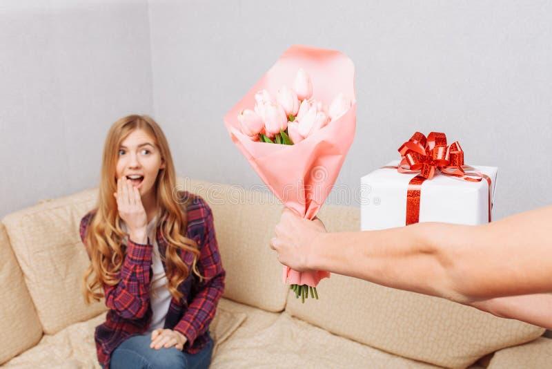 As mãos dão um ramalhete das tulipas e de um presente a uma menina chocada que senta-se em casa no sofá foto de stock royalty free
