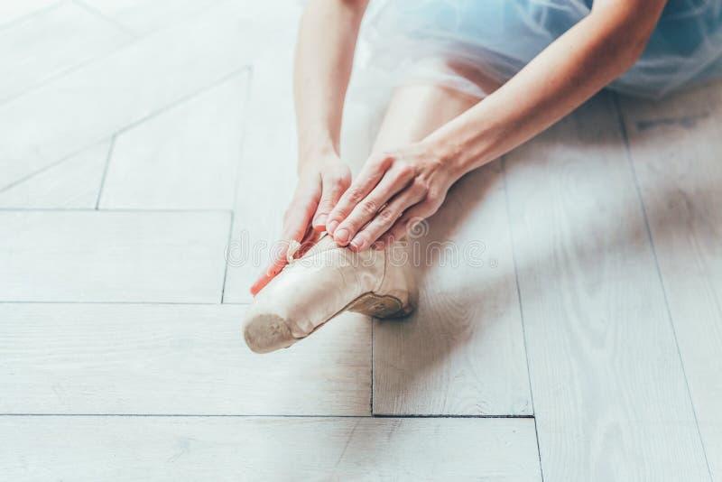 As mãos da bailarina põem sapatas do pointe sobre o pé na classe de dança imagem de stock