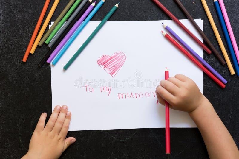 As mãos da criança com lápis tiram o coração no Livro Branco Conceito do dia do ` s da matriz celebration Cartão feito à mão Vist imagens de stock