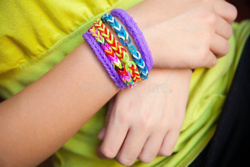 As mãos da criança com o tear de borracha colorido do arco-íris unem o bracelete fotografia de stock royalty free
