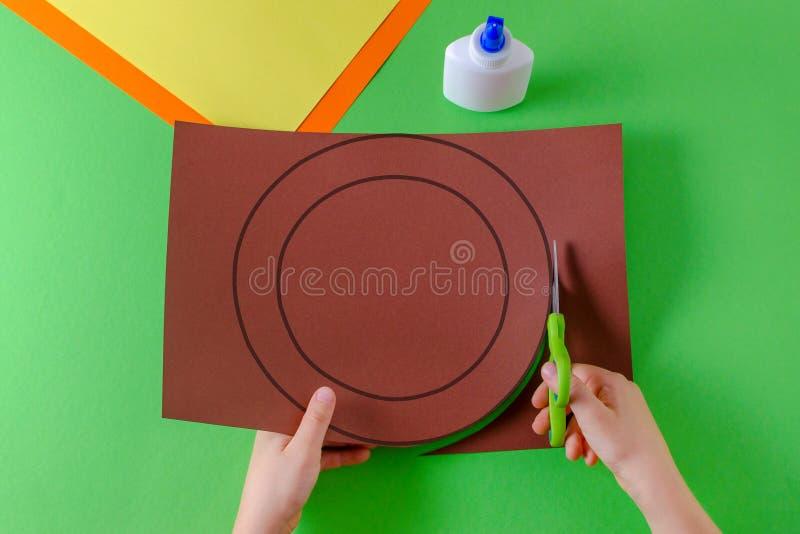 As mãos da criança cortaram o círculo no papel marrom com tesouras, vista superior, no verde imagens de stock royalty free