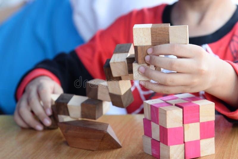 As mãos da criança que jogam com os tijolos de madeira coloridos Menino da criança de 5 anos que joga o enigma de madeira do brin fotos de stock royalty free