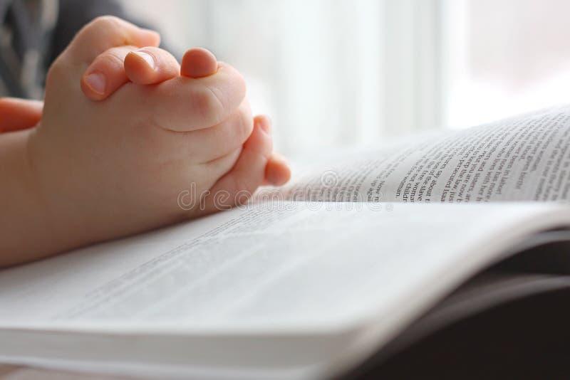 As mãos da jovem criança que rezam na Bíblia Sagrada