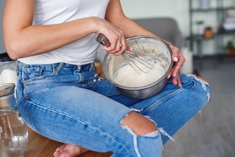 As mãos da jovem mulher na roupa ocasional amassam uma massa em uma placa de metal na cozinha à moda Mulher bonita nova que coze  imagens de stock