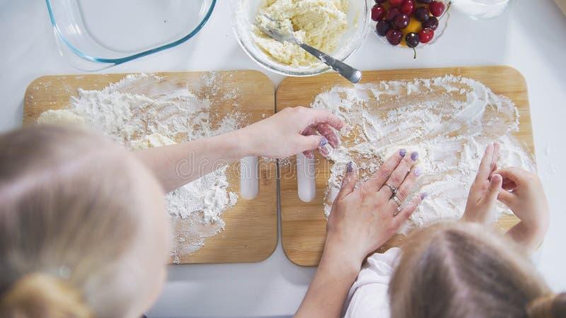 As mãos da mamã e da filha polvilham a farinha na placa para preparar panquecas fotos de stock