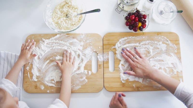 As mãos da mamã e da filha polvilham a farinha na placa para preparar panquecas imagens de stock royalty free