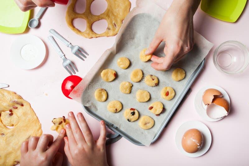 As mãos da mamã espalharam cookies caseiros no papel de pergaminho para cozer Minha filha faz uma cookie Conceito das cookies do  imagens de stock