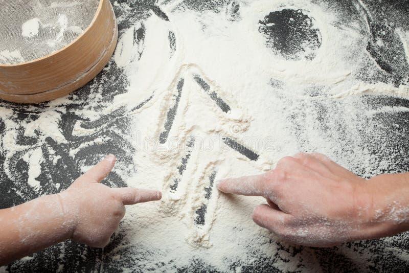 As mãos da mamã tiram com a filha de uma árvore de Natal na farinha, preparação comum das cookies fotografia de stock royalty free